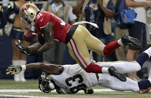 San Francisco 49ers safety Donte Whitner, top, intercepts a pass as St. Louis Rams wide receiver Brian Quick, bottom, watches, before falling into the end zone for a touchback during the second quarter of an NFL football game Thursday, Sept. 26, 2013, in St. Louis. (AP Photo/Charlie Riedel)