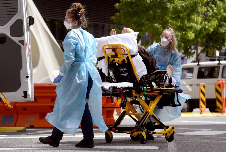 Medical staff transport a patient from the Royal Melbourne Hospital in Melbourne.