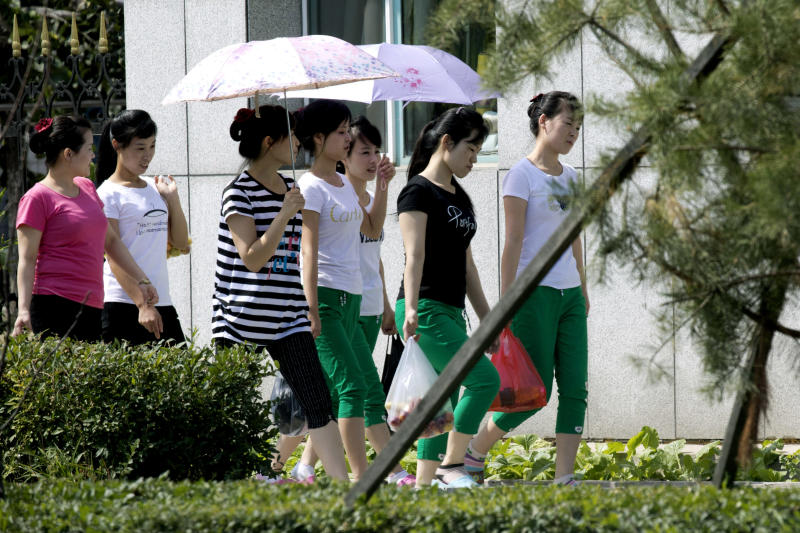 In this Sept. 2, 2017, photo, North Korean workers walk into the Hong Chao Zhi Yi garment factory after visiting a street market in the city of Hunchun in northeastern China's Jilin province. Roughly 3,000 North Koreans are believed to work in Hunchun, a far northeast Chinese industrial hub just a few miles from the borders of both North Korea and Russia. (AP Photo/Ng Han Guan)