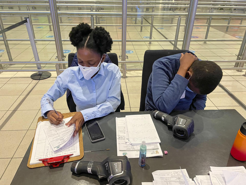 South African health ministry officials collect tracing forms from international travelers at Johannesburg's OR Tambo airport Monday Dec. 21 2020. More and more countries around the world are restricting travel from Britain and elsewhere, including South Africa, amid concerns about new strains of the coronavirus. (AP Photo/Jerome Delay)