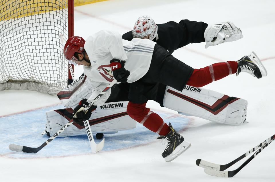 Arizona Coyotes center Nick Schmaltz, front, scores a goal against Coyotes goaltender Darcy Kuemper, back, during NHL hockey practice at Gila River Arena Monday, July 13, 2020, in Glendale, Ariz. (AP Photo/Ross D. Franklin)