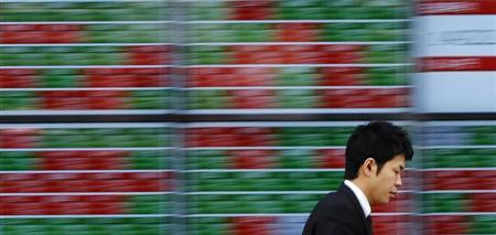 A pedestrian walks past electronic boards showing stock prices outside a brokerage in Tokyo