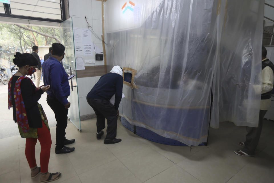 People stand in a queue for making enquiries from a reception covered in a plastic sheet as a precaution against COVID-19 at a municipal office in New Delhi, India, Friday, Nov. 6, 2020. A thick quilt of smog lingered over the Indian capital and its suburbs on Friday, fed by smoke from raging agricultural fires that health experts worry could worsen the city's fight against the coronavirus. Air pollution in parts of New Delhi have climbed to levels around nine times what the World Health Organization considers safe, turning grey winter skies into a putrid yellow and shrouding national monuments. (AP Photo/Manish Swarup)