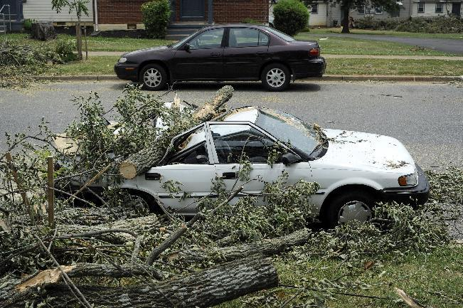 A car sits, crushed by a fallen tree, on Carrington Road in Lynchburg, Va., July 1, 2012. Two days after storms tore across the eastern U.S., power outages were forcing people to get creative to stay cool in dangerously hot weather. Temperatures approached 100 degrees in many storm-stricken areas, and utility officials said the power will likely be out for several more days. (AP Photo/The News & Advance, Parker Michels-Boyce)