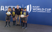 Australian rugby player Reece Hodge poses for a photo with young players at a media event in Sydney where Australia formally announced its bid to host the 2027 Rugby World Cup, Thursday, May 20, 2021. It would be the third time the sport's showcase event would be held in the country. (AP Photo/Mark Baker)