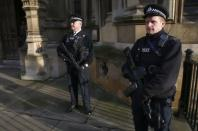Armed police officers stand on duty outside the Houses of Parliament in Westminster, central London November 24, 2014. REUTERS/Andrew Winning