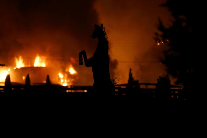 A horse statue is silhouetted by a burning structure during the wind-driven Kincade Fire in Windsor, California, Oct. 27, 2019. (Photo: Stephen Lam/Reuters)