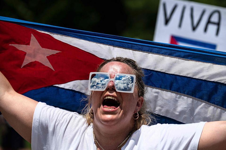A demonstrator holds the Cuban flag while protesting in front of the White House in Washington, DC, on July 12, 2021.