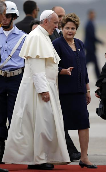 Brazil's President Dilma Rousseff, right, talks to Pope Francis as she accompanies him upon his arrival at the international airport in Rio de Janeiro, Brazil, Monday, July 22, 2013. During his seven-day visit, Francis will meet with legions of young Roman Catholics converging on Rio for the church's World Youth Day festival. (AP Photo/Jorge Saenz)