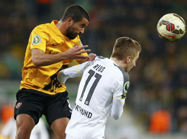 Borussia Dortmund's Marco Reus (R) and Dynamo Dresden's Nils Teixeira jump for a header during their German Cup (DFB Pokal) soccer match in Dresden March 3, 2015. REUTERS/Hannibal Hanschke (GERMANY - Tags: SOCCER SPORT) DFB RULES PROHIBIT USE IN MMS SERVICES VIA HANDHELD DEVICES UNTIL TWO HOURS AFTER A MATCH AND ANY USAGE ON INTERNET OR ONLINE MEDIA SIMULATING VIDEO FOOTAGE DURING THE MATCH.