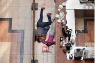 <p>2013. A woman shelters her children on the floor of the the Westgate Mall during an attack by militants in Nairobi.</p>