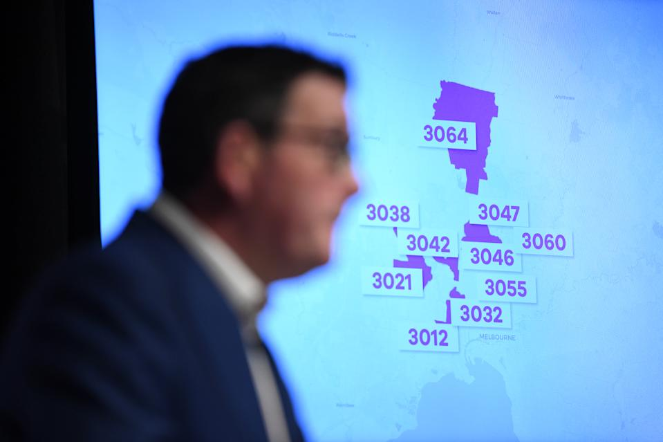 Postcodes of Melbourne suburbs are seen on a television screen as Victorian Premier Daniel Andrews speaks to media.