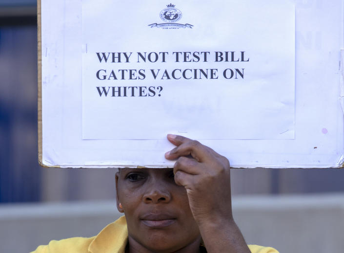 A woman holds a placard to protest against Coronavirus trials in Africa, outside the University of the Witwatersrand in Johannesburg, South Africa, Wednesday, July 1, 2020. A protest against Africa's first COVID-19 vaccine trial is underway as experts note a worrying level of resistance and misinformation around testing on the continent. (AP Photo/Themba Hadebe)