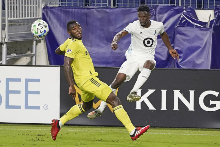 Minnesota United defender Bakaye Dibassy, right, passes the ball past Nashville midfielder Brian Anunga during the second half of an MLS soccer match Tuesday, Oct. 6, 2020, in Nashville, Tenn. (AP Photo/Mark Humphrey)