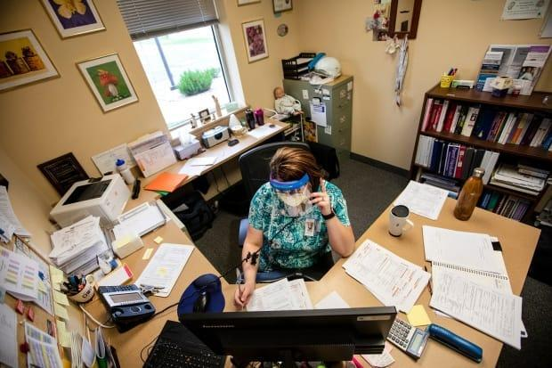 A public health nurse conducts a contact tracing phone call in Wyoming in this July file photo.  (Mike Moore/Gillette News Record/The Associated Press - image credit)