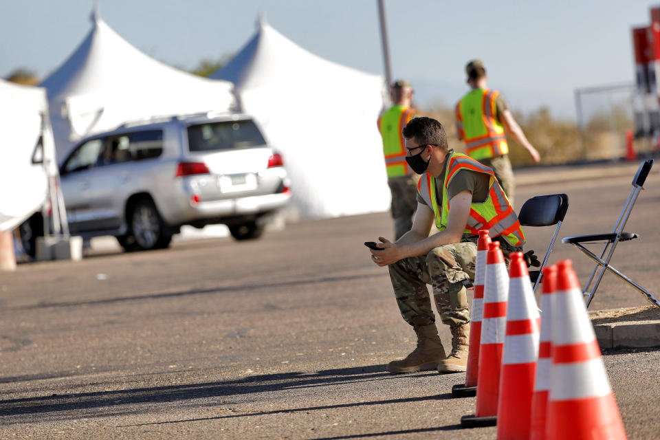 A National Guard solider waits to direct traffic as only one vehicle with people pulls up to be tested for the COVID-19 Coronavirus Tuesday, July 28, 2020 at South Mountain Park in Phoenix. It was the last day of a 12-day blitz aimed at bringing tens of thousands of COVID-19 tests to underserved Latino communities in Phoenix but only 14,000 of some 55,000 tests were administered at the park and the western neighborhood of Maryvale, leaving more than 40,000 COVID-19 test kits unused. (AP Photo/Matt York)