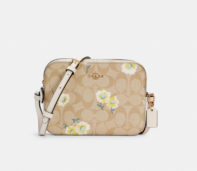 Mini Camera Bag In Signature Canvas With Daisy Print. Image via Coach Outlet.