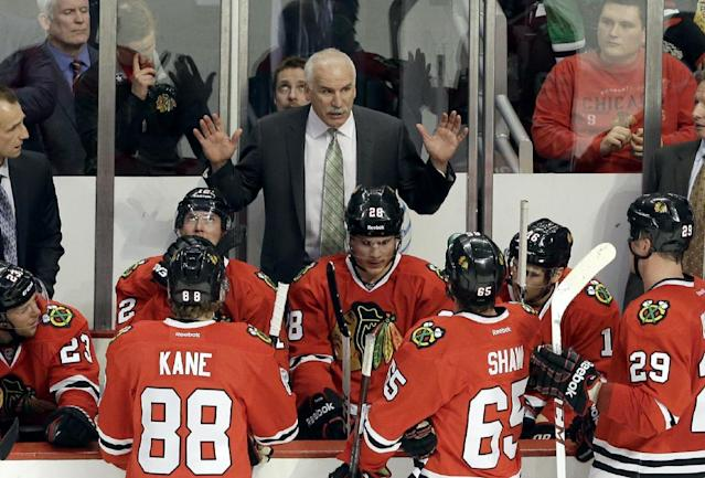Chicago Blackhawks head coach Joel Quenneville, top, talks to his team during the third period of an NHL hockey game against the Nashville Predators in Chicago, Friday, March 14, 2014. The Predators won 3-2. (AP Photo/Nam Y. Huh)