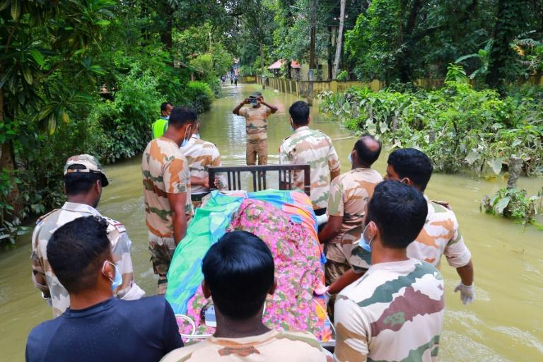Indian rescue workers transport a bed with an elderly sick woman as she is moved from her home in a waterlogged area to a relief camp in Chengannur