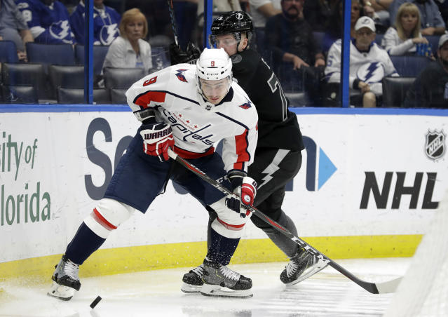Washington Capitals defenseman Dmitry Orlov (9) beats Tampa Bay Lightning left wing Adam Erne (73) to a loose puck during the second period of an NHL hockey game Saturday, March 30, 2019, in Tampa, Fla. (AP Photo/Chris O'Meara)