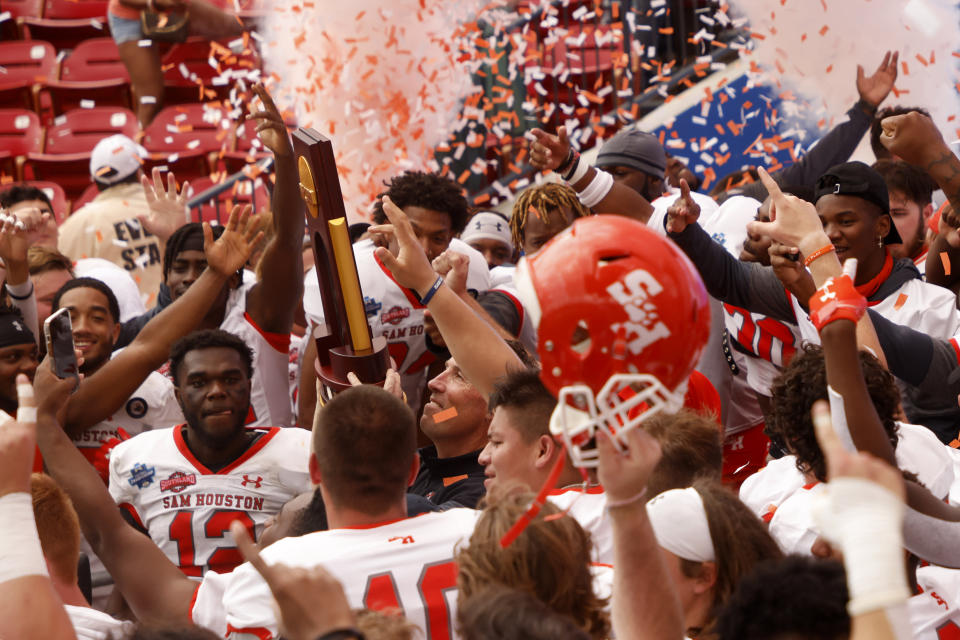 Sam Houston State head coach K.C. Keeler hoists the championship trophy after defeating South Dakota State 23-21 for the NCAA college FCS Football Championship in Frisco, Texas, Sunday, May 16, 2021. (AP Photo/Michael Ainsworth)