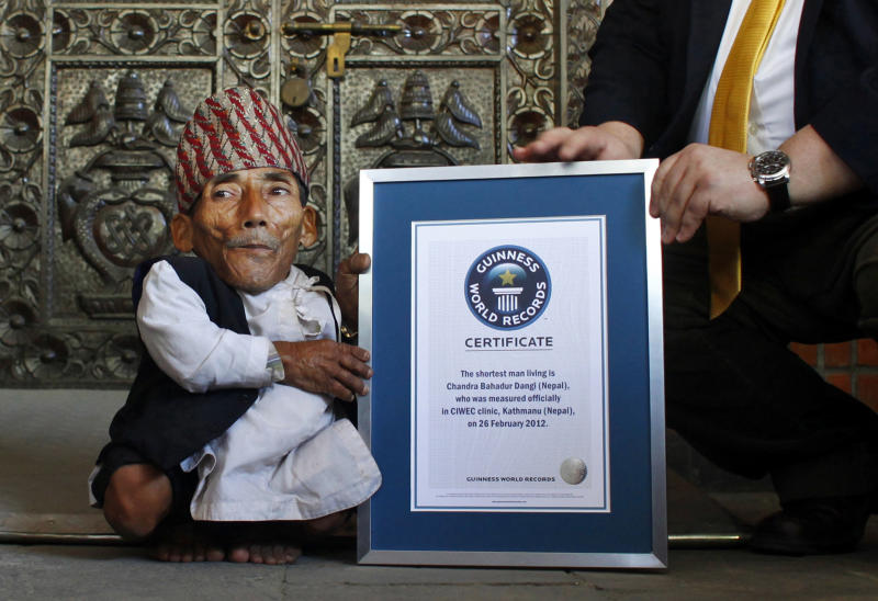 Nepal's Chandra Bahadur Dangi is given a certificate by Editor-in-Chief of Guinness World Records, Craig Glanday, after being declared the world's shortest living man and shortest man ever by the Guinness Book of Records, at a ceremony in Katmandu, Nepal, Sunday, Feb. 26, 2012. The 72-year-old man was measured at just 21.5 inches (54.6 centimeters) tall has been declared the shortest person to be recorded by the Guinness World Records snatching the title from Junrey Balawing of the Philippines, who is 23.5 inches (60 centimeters) tall. (AP Photo/Niranjan Shrestha)