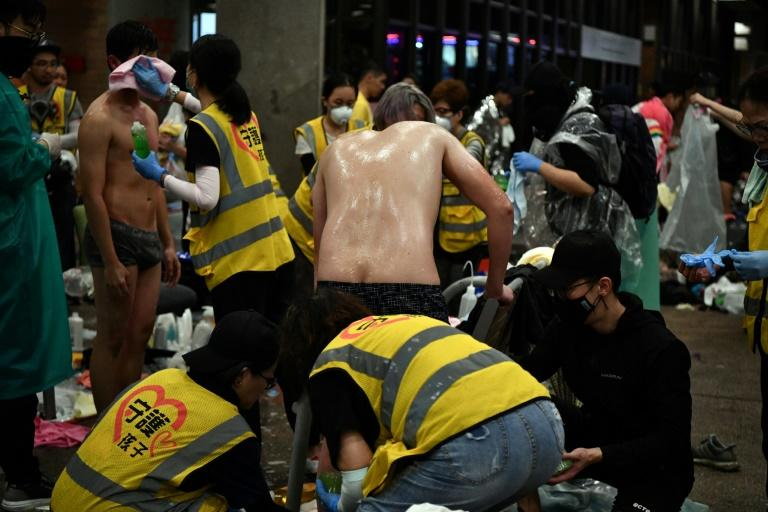 Anti-government protesters sprayed by pepper-water and teargas being treated by volunteer medics the Polytechnic University of Hong Kong (AFP Photo/Anthony WALLACE)