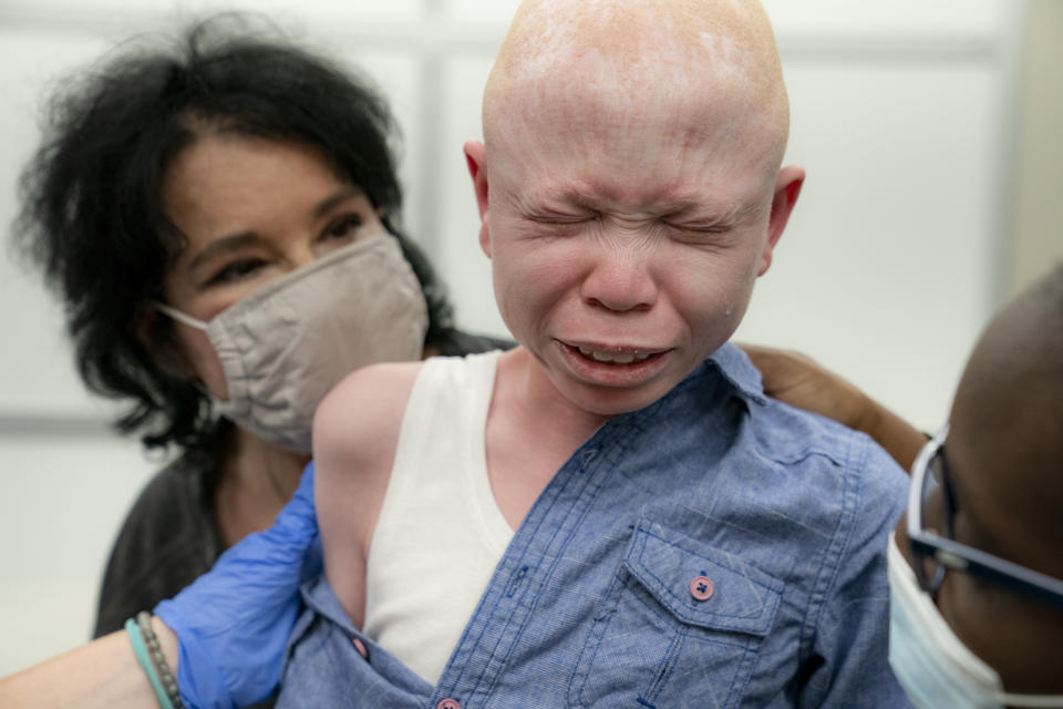Baraka Cosmas, 12, cries on the lap of Elissa Montanti, founder and director at The Global Medical Relief Fund, left, after he receives a COVID-19 vaccination at Richmond University Medical Center, Friday, June 4, 2021, in the Staten Island borough of New York. Some of the children brought to the hospital in Montanti's group, all amputees who have faced severe trauma in their lives, were nervous before receiving the injection in an unfamiliar setting. (AP Photo/John Minchillo)