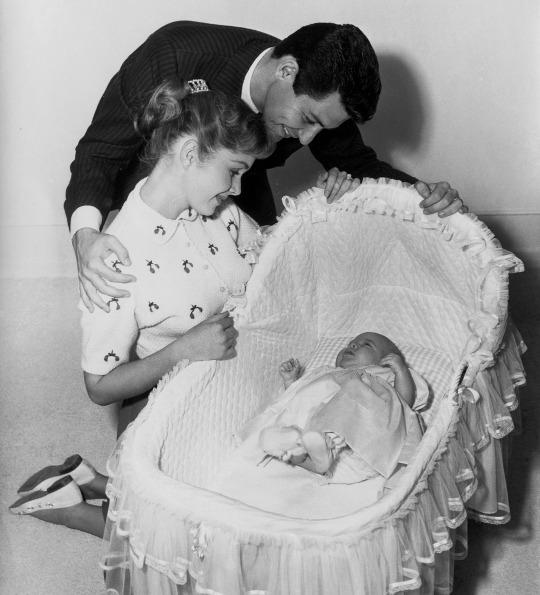 <p>Eddie Fisher and Debbie Reynolds gaze at their newborn daughter, Carrie Francis Fisher, in the first picture of the family together. The couple welcomed Carrie on Oct. 21, 1956. (Photo: George Rinhart/Corbis via Getty Images) </p>