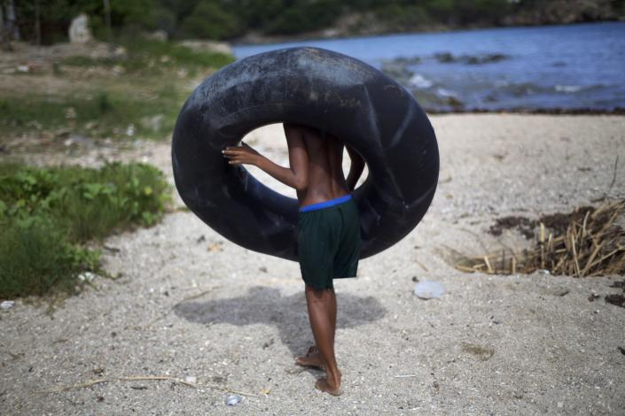 A youth carries a rubber float on the beach in Guama, Cuba, Friday, Aug. 24, 2012. Tropical Storm Isaac strengthened slightly as it spun toward the Dominican Republic and vulnerable Haiti on Friday, threatening to bring punishing rains but unlikely to gain enough steam to strike as a hurricane. Cuba declared a state of alert Friday for six eastern provinces. (AP Photo/Ramon Espinosa)