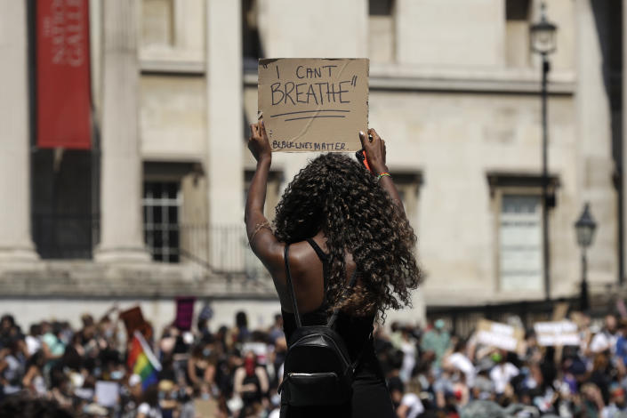 A woman holds up a banner as people gather in Trafalgar Square in central London on Sunday, May 31, 2020 to protest against the recent killing of George Floyd by police officers in Minneapolis that has led to protests across the US. (AP Photo/Matt Dunham)