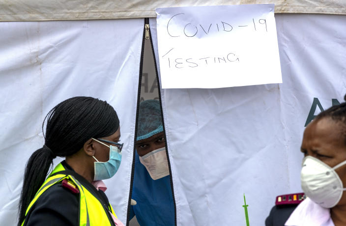 A health worker wearing personal protective gear inside a testing tent, gestures colleagues during the screening and testing for COVID-19, in Lenasia, south of Johannesburg, South Africa, Wednesday, April 8, 2020. South Africa and more than half of Africa's 54 countries have imposed lockdowns, curfews, travel bans or other restrictions to try to contain the spread of COVID-19. The new coronavirus causes mild or moderate symptoms for most people, but for some, especially older adults and people with existing health problems, it can cause more severe illness or death. (AP Photo/Themba Hadebe)