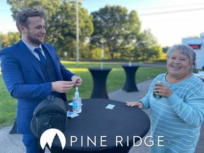 A Pine Ridge resident enjoys a laugh with local magician, Evan Priem, at the Pine Ridge ribbon cutting ceremony.