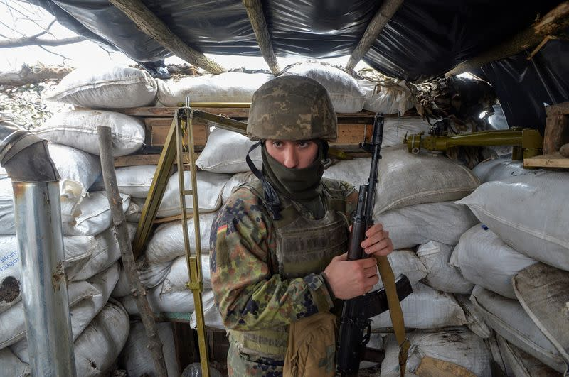 FILE PHOTO: A service member of the Ukrainian armed forces stands guard at fighting positions in Luhansk Region
