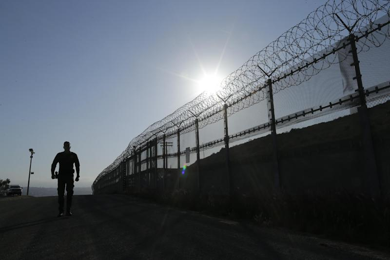 FILE--In this June 22, 2016, file photo, a Border Patrol agent walks along a border structure in San Diego, Calif. The U.S. Border Patrol's parent agency may exempt many veterans and law enforcement officers from a requirement that new hires take a lie-detector test. (AP Photo/Gregory Bull, file)