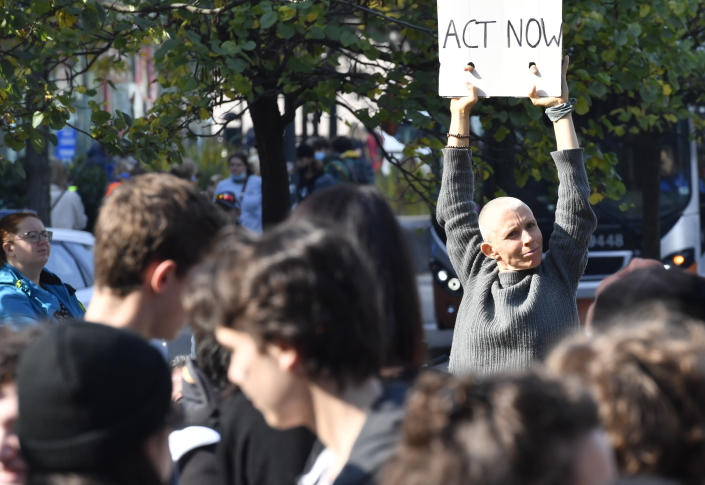 A protestor holds up a sign during a climate march in Brussels, Sunday, Oct. 10, 2021. Some 80 organizations are joining in a climate march through Brussels to demand change and push politicians to effective action in Glasgow later this month.(AP Photo/Geert Vanden Wijngaert)