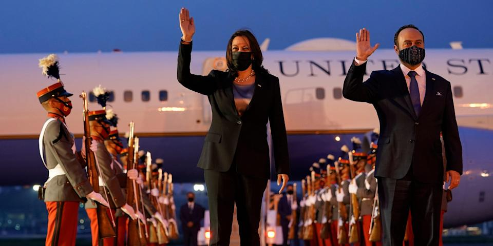 Kamala Harris Pedro Brolo stand in front the Guatemalan Air Force Central Command at night, waving.