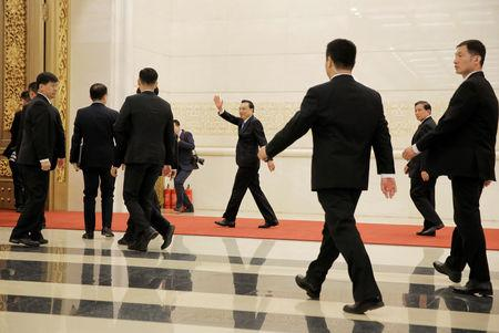 Chinese Premier Li Keqiang waves as he leaves at the end of a news conference following the closing session of the National People's Congress (NPC) at the Great Hall of the People in Beijing, China March 15, 2019. REUTERS/Thomas Peter