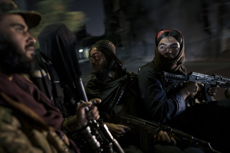 Taliban fighters ride in the back of a vehicle during a night patrol in Kabul, Afghanistan, Sunday, Sept. 12, 2021. The Taliban are shifting from being warriors to an urban police force. (AP Photo/Felipe Dana)