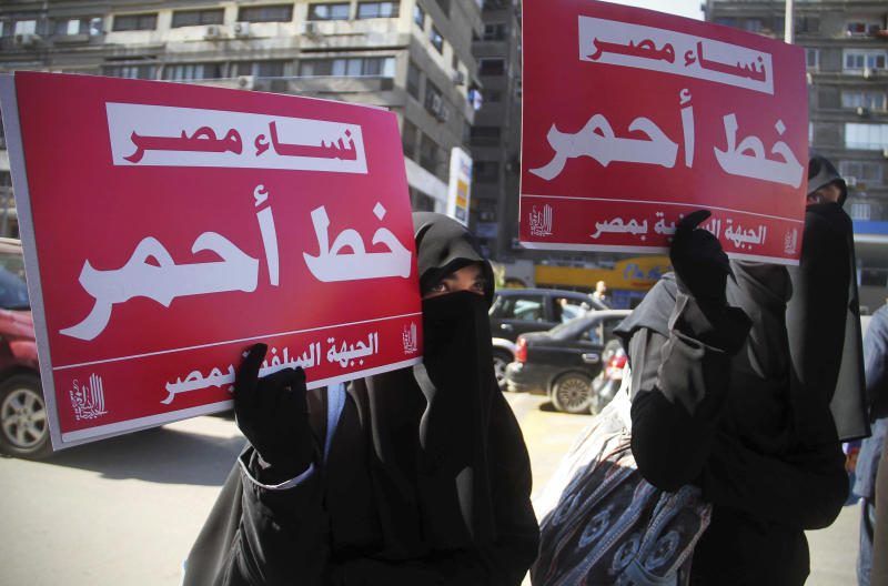 "FILE - In this Dec. 27, 2011 file photo, two women hold up banners in Arabic that read, ""Egyptian women, red line,"" during a rally supporting women's right in Cairo, Egypt.  The prosecution of a 15-year-old girl who killed a bus driver after he allegedly tried to rape her in July 2019 has reignited debate over the treatment of women in Egypt's legal system, including blaming female victims of sexual violence and the practice of administering virginity tests.(AP Photo/Ahmed Ali, File)"