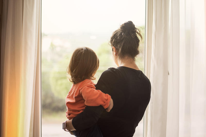 Mother and son looking out of window from home