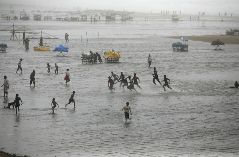 People play on the Marina beach flooded with sea water on the Bay of Bengal coast in Chennai, India, Wednesday, Oct. 31, 2012. More than 100,000 people were evacuated from their homes Wednesday as a tropical storm approached southern India from the Bay of Bengal, officials said the storm, with wind speeds of up to 100 kilometers (60 miles) per hour, was expected to reach land later Wednesday. (AP Photo/Arun Sankar K)
