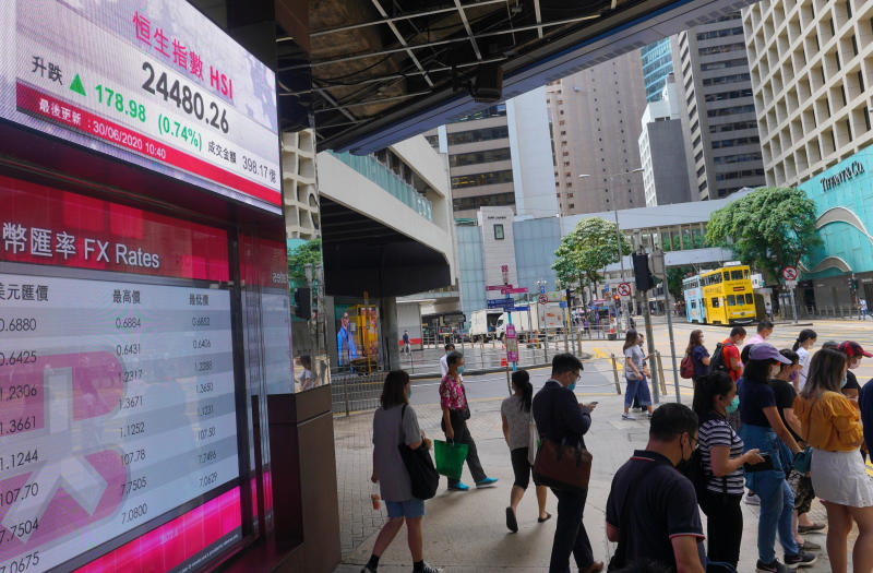People wearing a face mask walks past a bank's electronic board showing the Hong Kong share index at Hong Kong Stock Exchange Tuesday, June 30, 2020. Asian shares are rising, cheered by a rally on Wally Street that underlined some optimism about global business performance despite the ongoing coronavirus pandemic. (AP Photo/Vincent Yu)