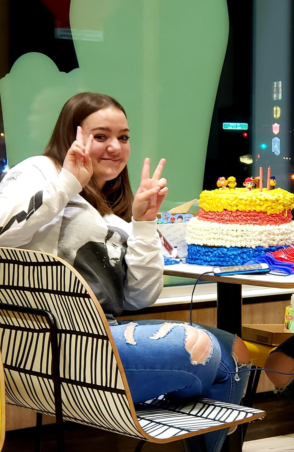 Kylie Leniz, who was fatally shot while working at McDonald's, smiles and holds up two peace signs with a cake.