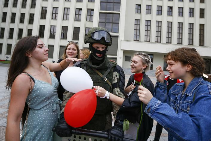 Women greet a soldier guarding the Belarusian Government building, in an exaggerated show of friendliness, in Minsk, Belarus, Friday, Aug. 14, 2020. Some thousands of people have gathered in the centre of the Belarus capital, Minsk, in a show of anger over a recent brutal police crackdown on peaceful protesters that followed a disputed presidential election. (AP Photo/Sergei Grits)