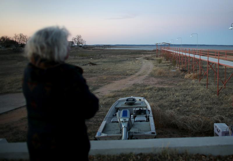 A woman looks at a pier once surrounded by the waters of Lake Buchanan on March 12, 2014 in Burnet, Texas (AFP Photo/Joe Raedle)