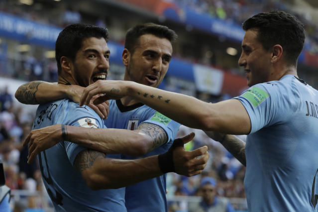 Uruguay's Luis Suarez , left, is greeted by teammates after scoring his team's opening goal during the group A match against Saudi Arabia at the 2018 soccer World Cup in Rostov Arena in Rostov-on-Don, Russia, Wednesday, June 20, 2018. (AP Photo/Andrew Medichini)