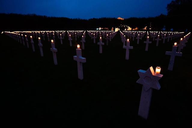 <p>Headstones with lighted candles are pictured at the Meuse-Argonne American Cemetery and Memorial on Nov. 11, 2017 in Romagne-sous-Montfaucon, eastern France, during the Armistice Day commemorations marking the end of World War One. 3500 of the 14,246 graves at the necropolis were illuminated with candles.(Photo: Jean-Christophe Verhaegen/AFP/Getty Images) </p>