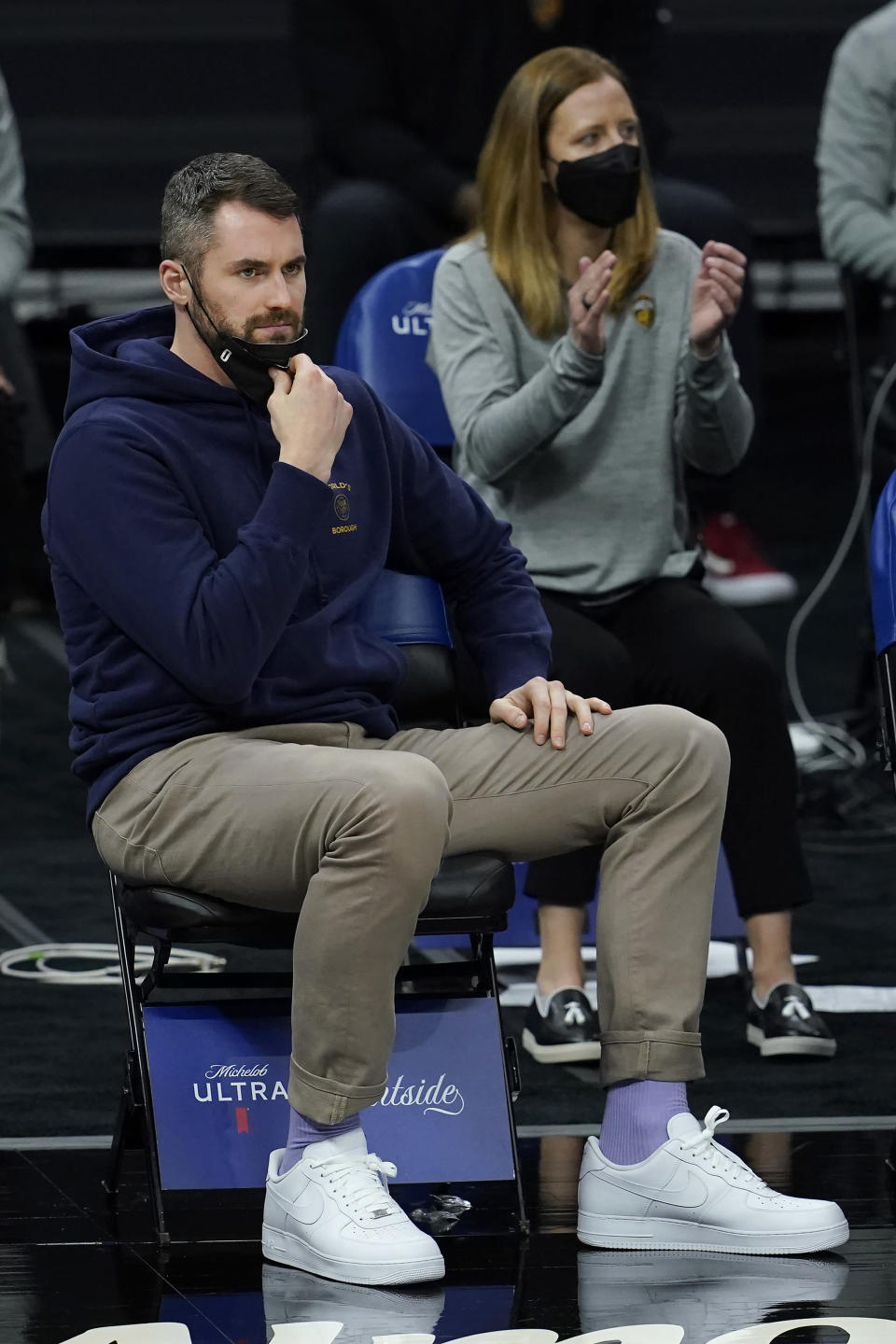 Injured Cleveland Cavaliers forward Kevin Love sits on the bench in front of assistant coach Lindsay Gottlieb during the second half of the team's NBA basketball game against the Sacramento Kings in Sacramento, Calif., Saturday, March 27, 2021. (AP Photo/Jeff Chiu)