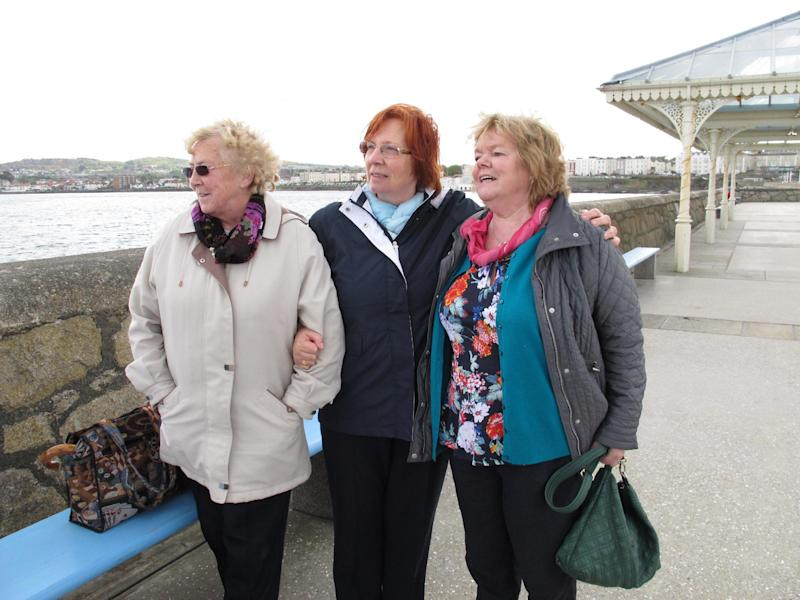 "In this May 13, 2013 photo, Marie Theresa Gill, center, poses with her friends Kathleen Greenhough, right, and Mary Murray at the pier in Dun Laoghaire in Dublin Co., after a wreath-laying ceremony to honor the so-called ""Forgotten Irish"" _the thousands of young Irish who emigrated to Britain during the 1950s and 1960s. Gill and Greenhough were among those emigrants. They returned as part of The Gathering, an effort by Ireland to bring its emigrants and their descendants home to honor them and their heritage. (AP Photo/Helen O'Neill)"